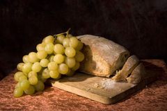 Bread loaf and grapes. Closeup of loaf of rustic bread and green grapes, black background stock images
