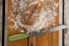 Bread loaf with knife on cutting board Stock Photo
