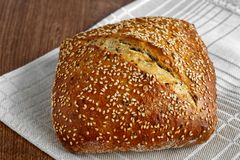 Bread loaf with sesame seeds. On a linen napkin royalty free stock image