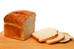 Bread loaf and slices. Loaf of bread with slices on a wooden food preparation board Royalty Free Stock Photography