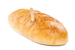 Bread loaf and wheat ear on white background. Royalty Free Stock Images