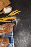 Bread loaf with wheat grains and flour Stock Photography
