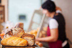 Bread Loafs On Counter With Woman Empting Create In Background Stock Photography
