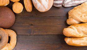 Bread loaves and bagels frame. Top down view on dark wooden table with copy space surrounded by freshly baked french bread, rolls, bagels and baguettes royalty free stock images