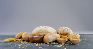 Bread loaves with wheat grains. Against grey background stock video