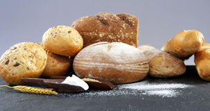 Bread loaves with wheat grains and flour. Against grey background stock video footage