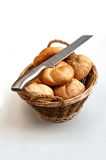 Bread loaves in a wicker basket with knife on top Royalty Free Stock Images