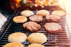 Bread and meat cooked for burgers outdoors on grill royalty free stock photography