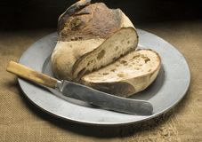 Bread on metal plate. With knife Stock Images