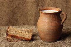 Bread and milk. Jug with milk and black bread lie on a sacking Royalty Free Stock Image
