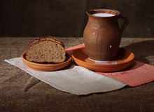 Bread and milk. Brown bread in a clay bowl and crock with milk Stock Image