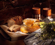 Bread and milk. Still life with fresh-backed round loaf, brown bread and clay cups with milk, simple rural meal; light painting Stock Photos
