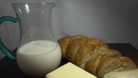 Bread, milk and butter on wooden table, close HD. Bread, milk and butter on wooden table, close stock video footage