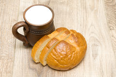 Bread and milk in a clay mug close-up Stock Images