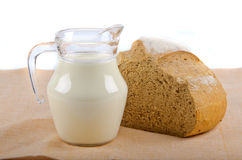 Bread and milk in pitcher Stock Images