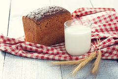 Bread and milk with spikelets of wheat on a cloth on a  boards Royalty Free Stock Photography