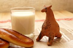 Bread and milk. On the table. Near folk clay toy Stock Photo
