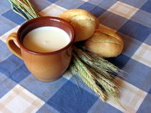 Bread, milk and wheat still-life. Bread loaves, mugful of milk and wheat straws on the table Stock Photography