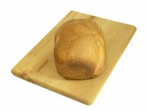 Bread n Bread Board. Loaf of home made bread on bread board isolated over white royalty free stock photo