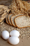 Bread nad three eggs. Bake goods and corn materials Stock Photography