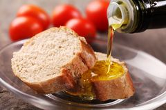 Bread and oil. Close-up of olive oil pouring on slices of bread Stock Photo