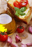 Bread, oil, garlic and tomatoes Stock Image