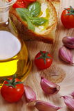 Bread, oil, garlic and tomatoes Stock Photos