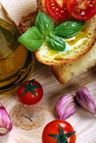 Bread, oil, garlic and tomatoes Stock Photography