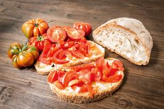 Bread oil, tomato, salt and pepper. Bread oil and tomato. Appetizing very fresh food typical of the Mediterranean diet, seasoned with the addition of salt and Royalty Free Stock Photo