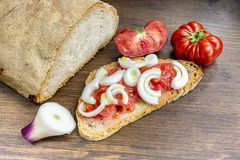 Bread, oil, tomato and Tropea onion. Bread, oil, tomato and onion have a fundamental part in the Mediterranean diet. In the specific case it is the Tropea onion Stock Photos