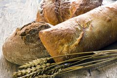 Bread on old wooden background. Bread with wheat ears on old wooden background Stock Photo