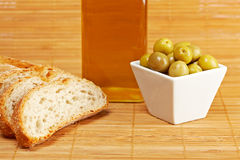 Bread, olive oil bottle and olives. Bread, olive oil bottle and some olives on wooden background. Shallow depth of field stock image