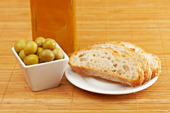 Bread, olive oil bottle and olives. Bread, olive oil bottle and some olives on wooden background. Shallow depth of field royalty free stock photo