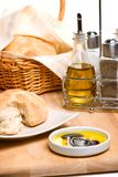 Bread, olive oil and spices. Pepper pot with black pepper, fresh bread, bottle of olive oil and spicy herbs on wooden cut board Stock Image