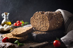 Bread, olive oil, tomato and basil on wooden cutting board Stock Photos