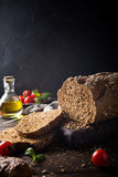 Bread, olive oil, tomato and basil on wooden cutting board Stock Photography
