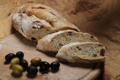 Bread with olives. Loaf of olive bread and bread slices with fresh olives on a chopping board Royalty Free Stock Photos