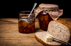 Bread and orange homemade jam on wooden table Stock Images