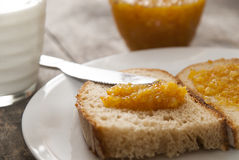 Bread with orange jam and glass of milk on wooden table. Close up photo Stock Photos