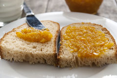 Bread with orange jam and glass of milk on wooden table Stock Photos
