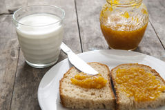Bread with orange jam and glass of milk on wooden table. Close up photo Stock Image
