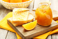 Bread and orange jam. On grey wooden background Royalty Free Stock Photo
