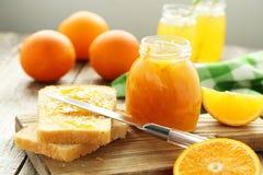 Bread and orange jam. On grey wooden background Stock Photos