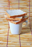 Bread over the cup on bamboo plate. Many slice of bread from whole wheat flour and white cup on bamboo plate stock photos