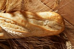 Bread over wooden table with wheat spikes Royalty Free Stock Photography