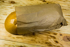 Bread packed in paper on wooden table Stock Photography