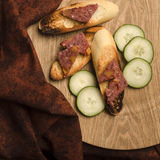 Bread and pate. Three toasted french bread covered with duck liver pate are displayed on a wodden plate with some cucumber slices, a nice brown cloth is places stock photography