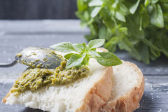 Bread with pesto, basil  on a wooden background Stock Photography