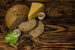The bread with a piece of cheese, decorated with leaves of salad and basil with cups of butter and honey are the wooden background. The bread and cut the slices Stock Images