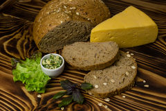 The bread with a piece of cheese, decorated with leaves of salad and basil with cups of butter are the wooden background. The bread and cut the slices with a Royalty Free Stock Photography